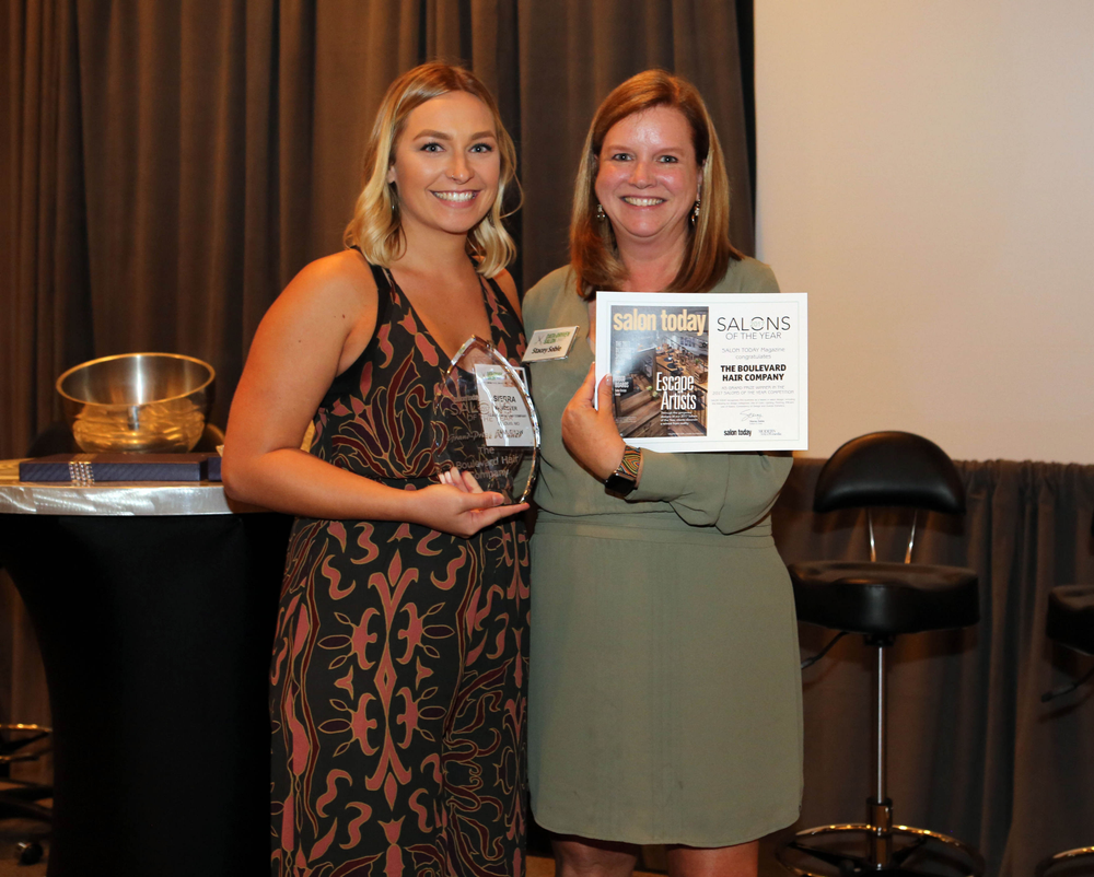 The Boulevard Hair Company's Sierra VanMeter accepts the 2017 Salons of the Year award from Stacey Soble