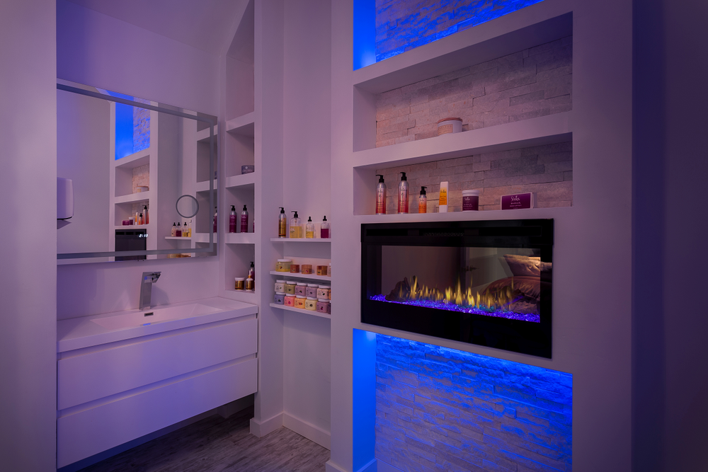 At Emma Justine Hair Lounge + Spa in Middletown, Kentucky, color comes in the the form of LED lighting surrounding the modern fireplace in the spa room.