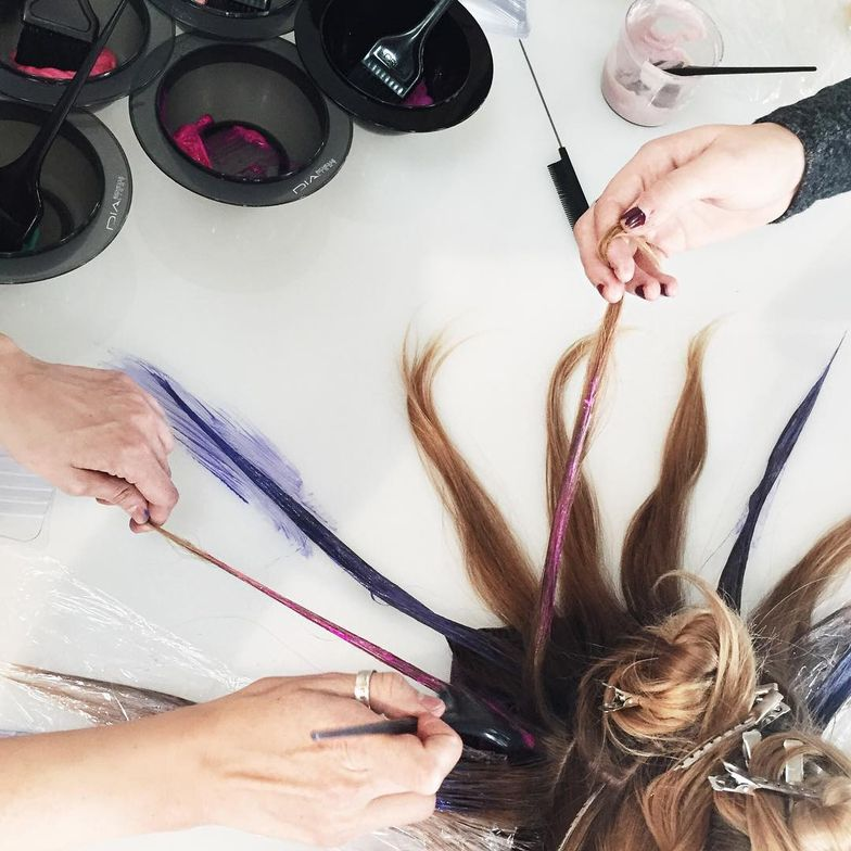 Stylists color the sectioned off hair on a color table.