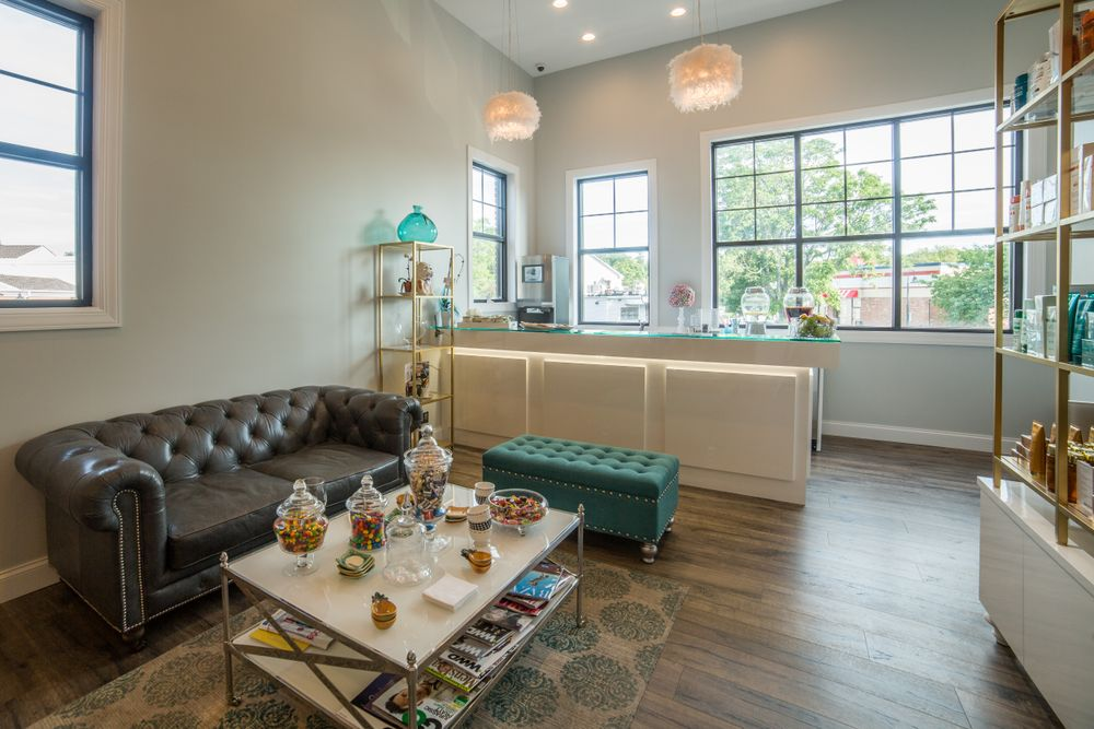 "The salon's client waiting area contains retail product shelving and a custom design full service ""refreshment bar"" that includes refrigeration and storage to provide beverages and snacks."