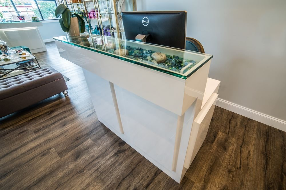 "A secondary ""Check Out Desk"" for client management and scheduling after salon visits features a removable glass top enabling the salon to change the display contents."