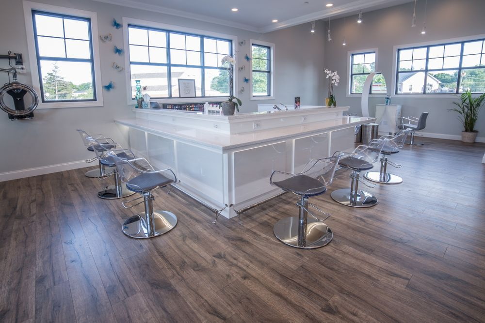 A custom designed color bar with product storage and the Salon Interiors Ghost chair. Instead of on-chair foot rests, the counter incorporates a floor mounted bar rail.