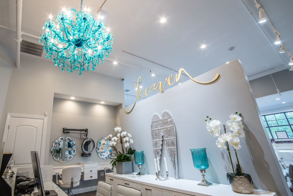 A turquoise chandelier and matching decorative glassware provide a fun splash of color that pops against the white surfaces of the furniture.