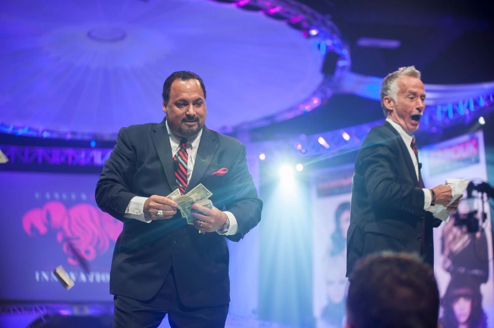 (L) Andre Chiavelli, executive vice president of sales, and (R) Scott Emery, senior vice president of international sales, throw money to the crowd during Saturday's general session.