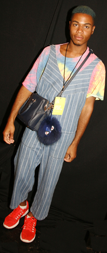Omari Francis, Fashion Stylist, with green hair, wearing a vintage tie dye shirt, Zara jumpsuit and bag, fur charm from Francesca, Nike flyknits, backstage at the Johny Dar Jeans for Refugees Show.<br />Photo: Helen Oppenheim