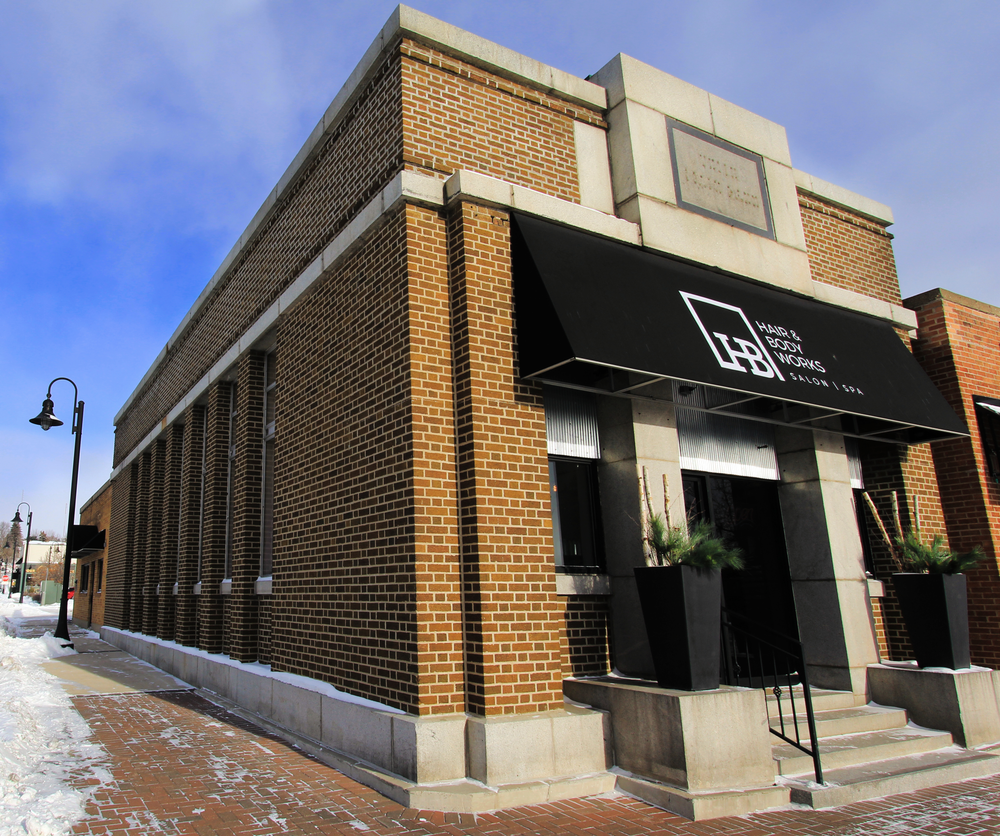 The brick exterior of Hair & Body Works in Sauk Rapids, Minnesota, offers a visual hint at the building's history as a former bank.
