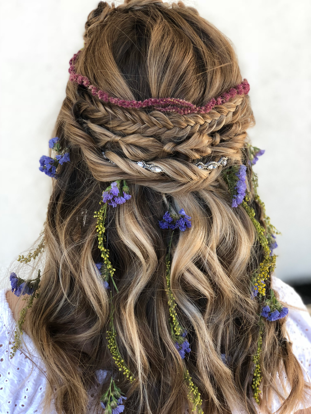 <p>Heather Schmick @heatherhairandbridalstylist: This look started with a sun-kissed balayage. Schmick used scruples clay lightener + scruples power blonde with B3 and 30 vol-using a chip brush/seran wrap and no heat. The hair was toned with Redken Shades EQ 8V/9GI and few drops of 9NA + clear then blow dried with round brush. The styling began with curling the hair in boho waves. To create the knots she made 3 flower braids, and for the bandana part she made a fish tail braid, a topsy braid with the rubber bands covered and twists that are twisted around a pink pewter hair band. To complete the look I finished it with a 3 strand braid and flowers to create a dream catcher effect and a flower crown.</p>