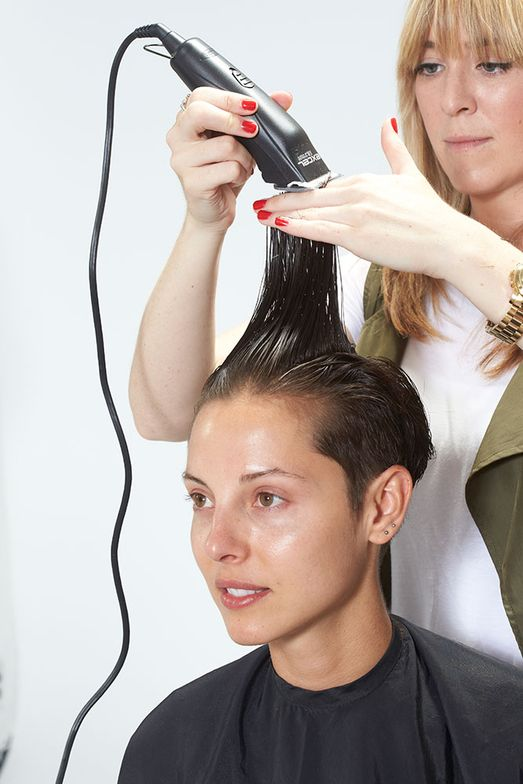 6. Lift hair up at the top. Using the clipper, cut straight across to remove the corner.