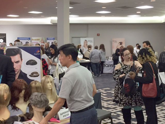 Participants checking out booths at HAIR+ Summit.