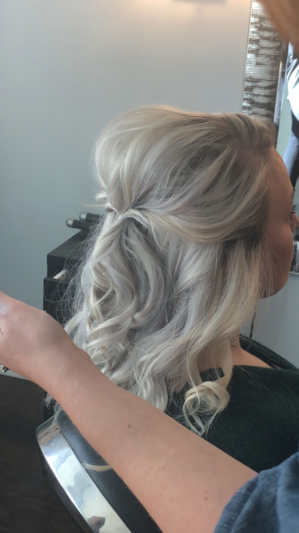 @lzhouseofhair began by curling the hair all around. She then blasted the hair with Living Proof's Dry Volume Spray and Design.Me's Dry Shampoo for Blondes. She next gathered two front pieces and twisted them to create volume before securing them with an elastic.