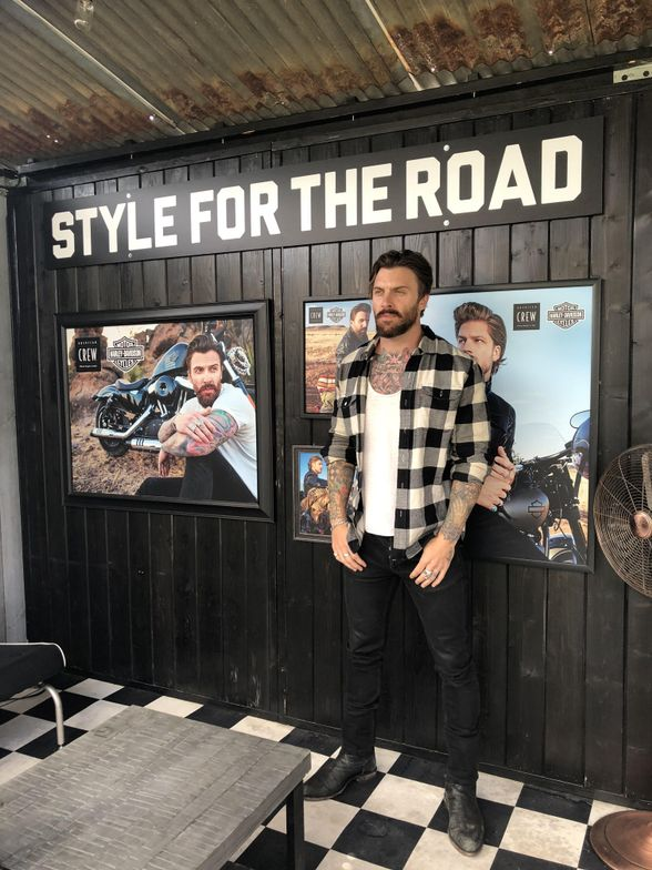 American Crew model, Levi, stands next to his picture in the American Crew pop-up barbershop.