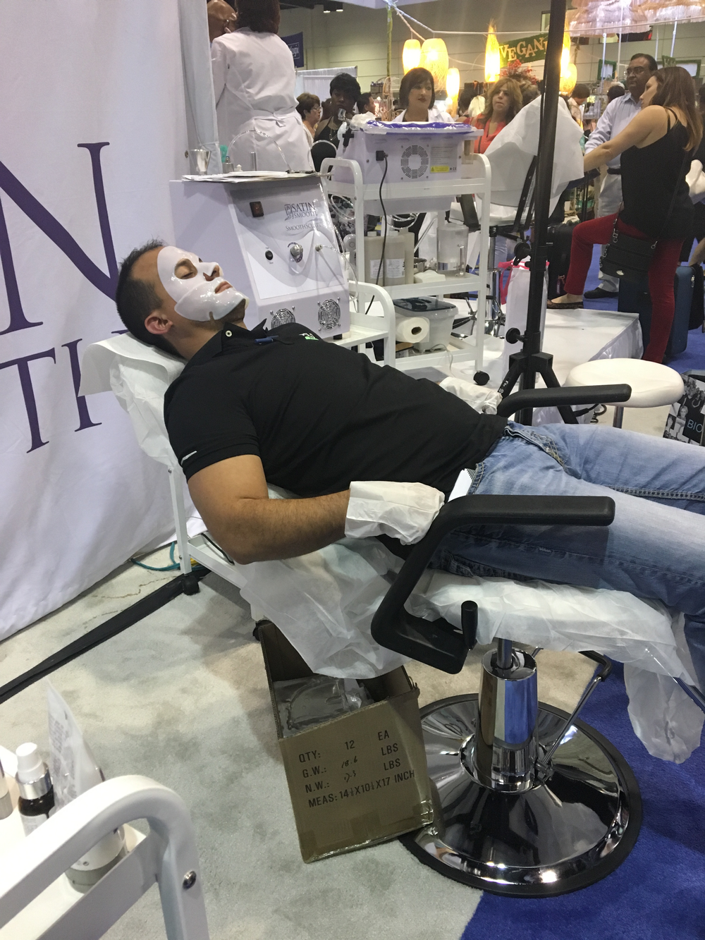 A show attendee relaxes with Satin Smooth collagen face and hand masks at the brand's booth, proving skincare isn't just for female clients.