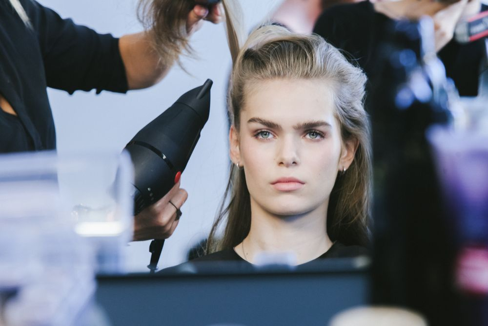 Blowdrying and directing hair upward for style.