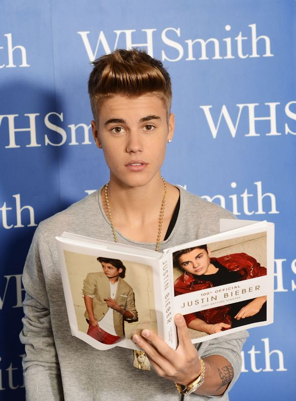 Justin Bieber poses with a copy of his new book during his 'Just Getting Started' book launch at the Congress Centre in London.