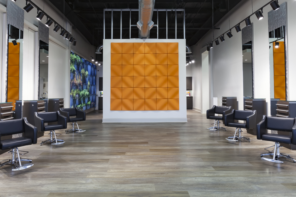 At Jyl Craven Hair Design in Canton, Georgia, muted orange acoustic tiles form a wall mural on the cutting floor while the greenery in the wall mural bring bright color into the shampoo room beyond.