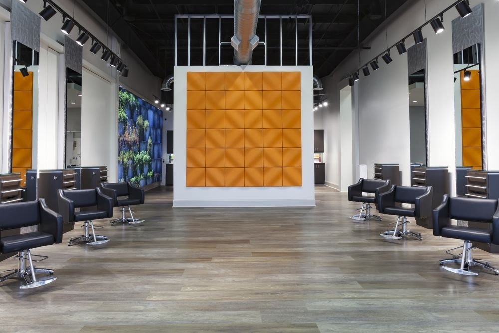 <p>At Jyl Craven Hair Design in Canton, Georgia, muted orange acoustic tiles form a wall mural on the cutting floor while the greenery in the wall mural bring bright color into the shampoo room beyond.</p>