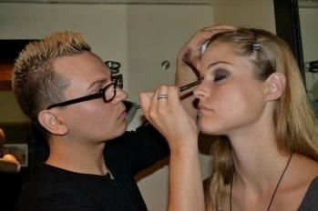 A student applies makeup to one of the models in the Vitamin Water Fashion Challenge.