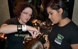 At the Vitamin Water Fashion Challenge, Karie Bennett demonstrates a technique for a student from the San Francisco Institute of Esthetics and Cosmetology A Paul Mitchell School.
