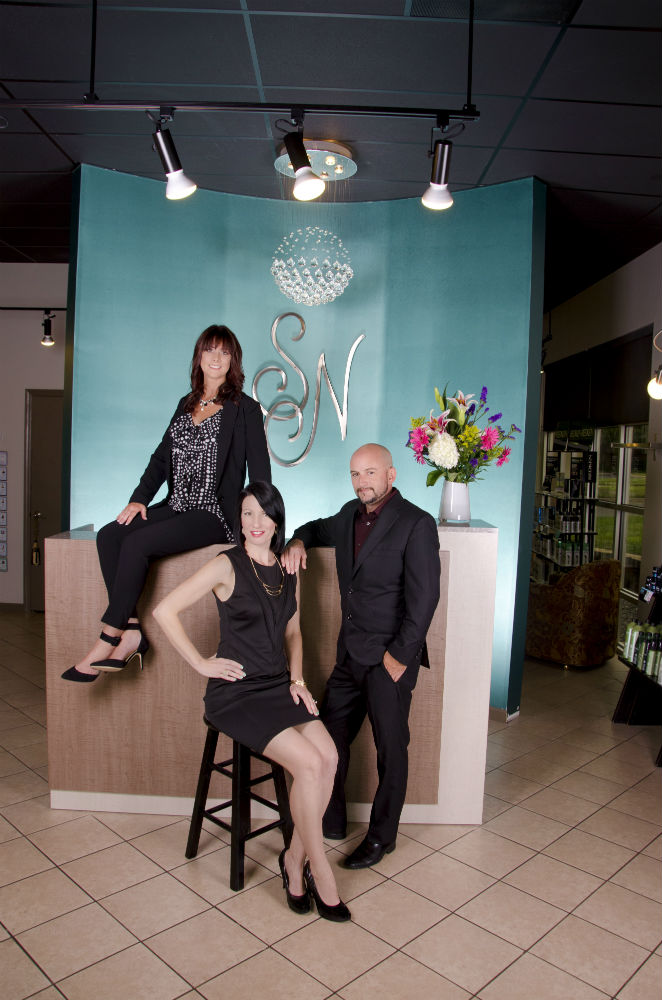 Kristi Valenzuela (on desk), head of Summit Salon Business Center's Front Desk Division, with clients Amy and Chris Naoum, co-owners of Salon Naman in Rock Hill, South Carolina. (photo credit: Rhiannon Mack) Rhiannon Mack