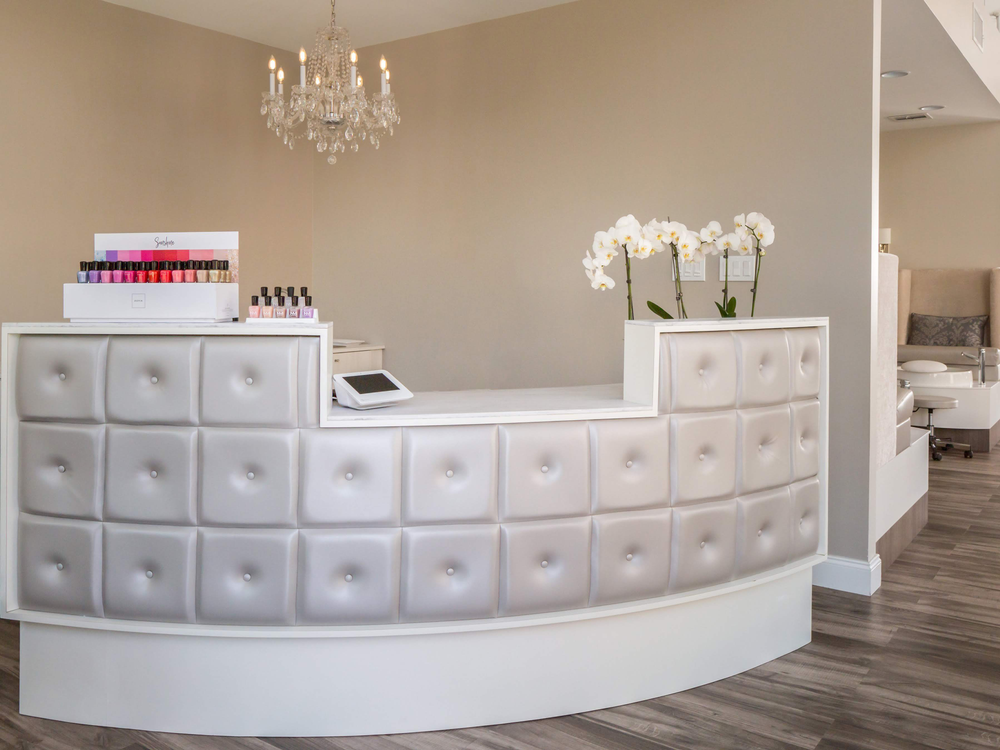 The leather tufted front desk and miniature chandelier tell guests their service will be an elevated experience.