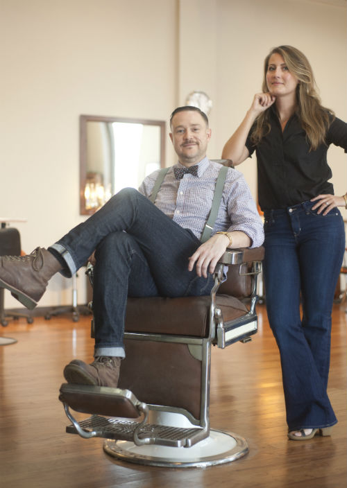 Local Honey owner Jay Bulluck with the salon's artistic director, Caitlin Brennan. Bulluck's sitting in of several Kochs & Paider vintage barber chairs he keeps at the salon along with other antiques and local artifacts.