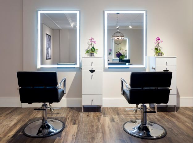<p>Lola has stylist stations with backlit LED mirrors.  The custom styling stations keep tools and wires contained and out of site, complete with purse hanger.  </p>