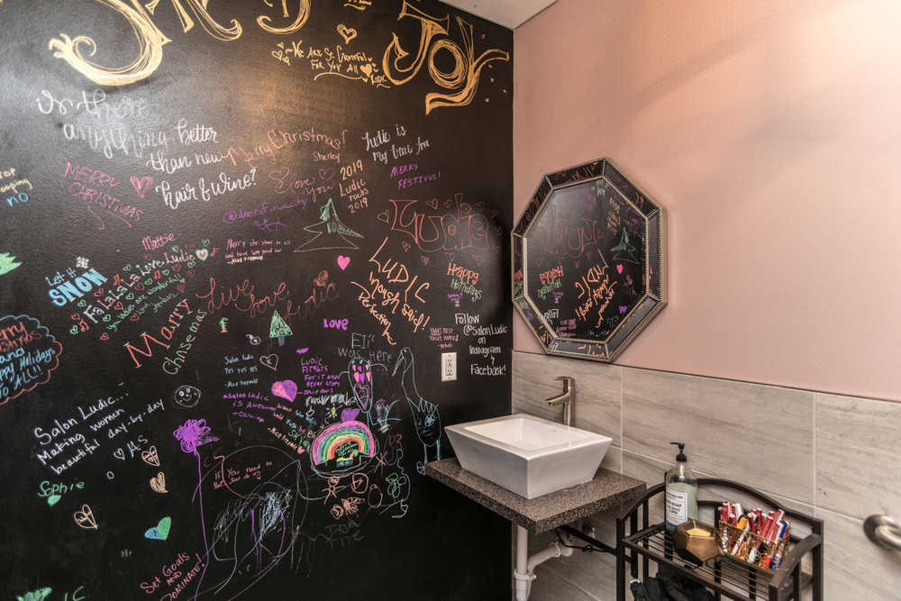 Clients bring the color to Salon Ludic in North Liberty, Iowa, where the bathroom chalk wall invites artistic expression.