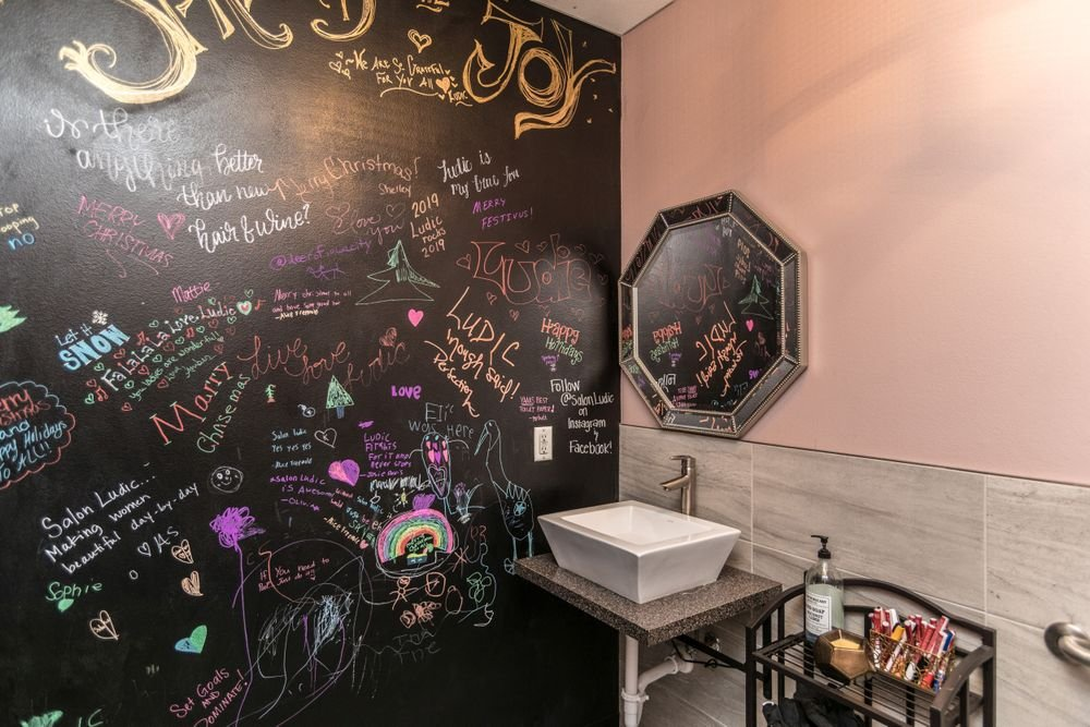 <p>Clients bring the color to Salon Ludic in North Liberty, Iowa, where the bathroom chalk wall invites artistic expression.</p>