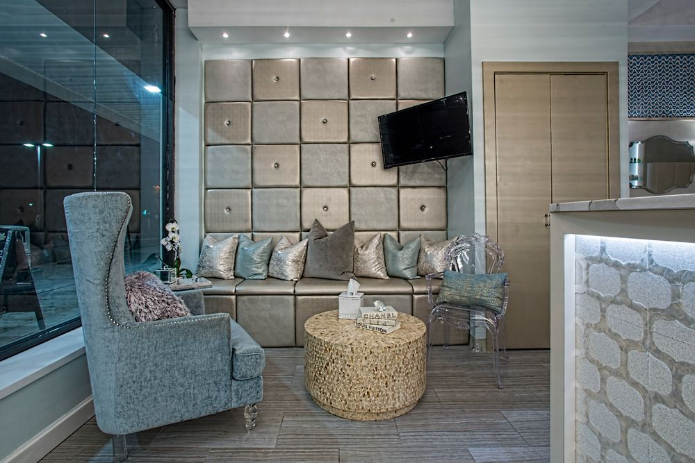 The waiting area duplicates the retail shelves with the same padded vinyl and button crystals to echo the effect of the chandelier and beaded reception desk panels.