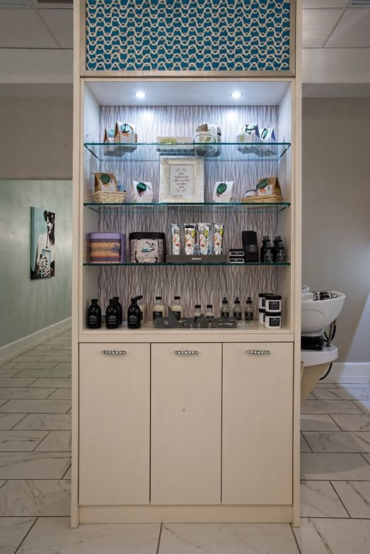 A custom designed dividing cabinet allows for additional product display and creates a sense of calm seclusion for shampoo and scalp treatments.