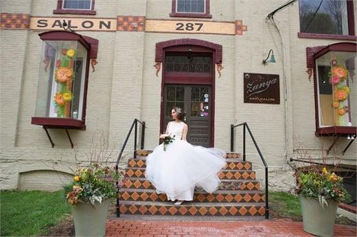 A bride poses on the step of Zanya Spa Salon in Lambertville, NJ.
