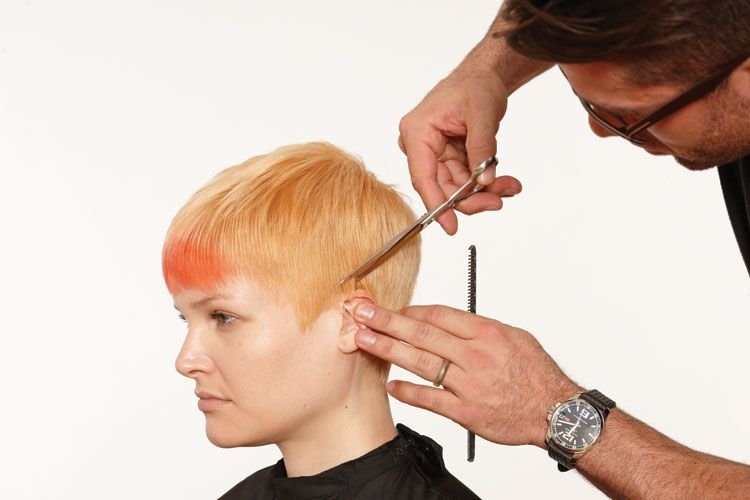 6. Comb the hair as it is to be worn. Begin the cut around the front of the ear. Cut against the skin to define the line.