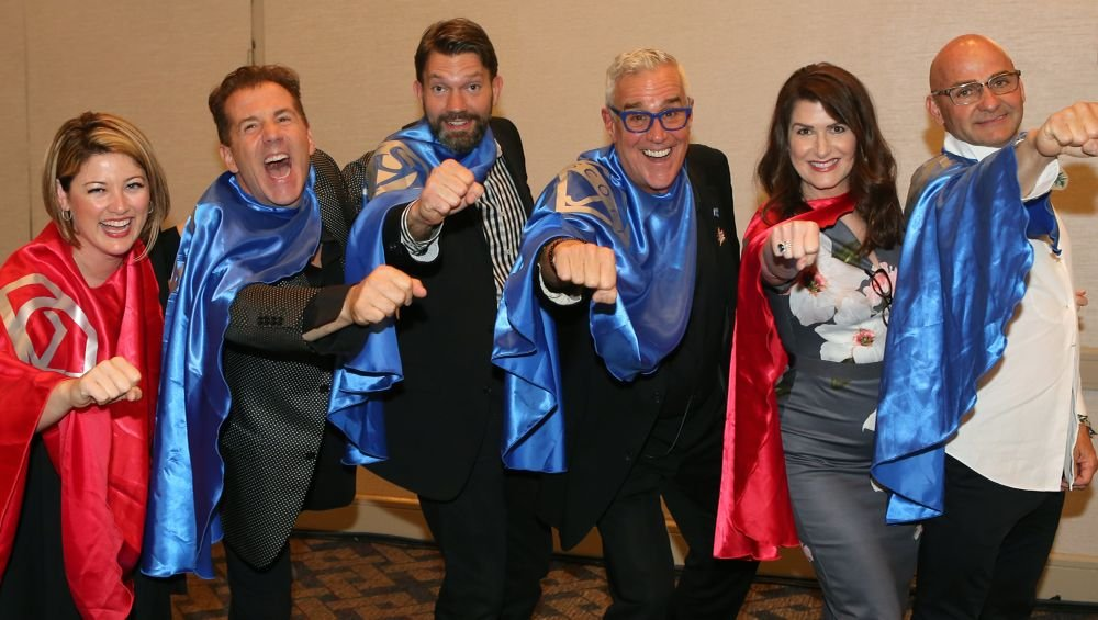 <p>The Manager Match-Up panelists demonstrate the power of strong owner-manager duos by donning superhero capes.</p>