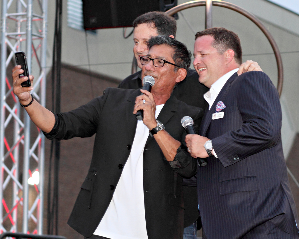 Modern Salon's Steve Reiss, Sam Villa and Minerva's Jay Rawl take a selfie on stage while kicking off the party of the century at Minerva's headquarters.
