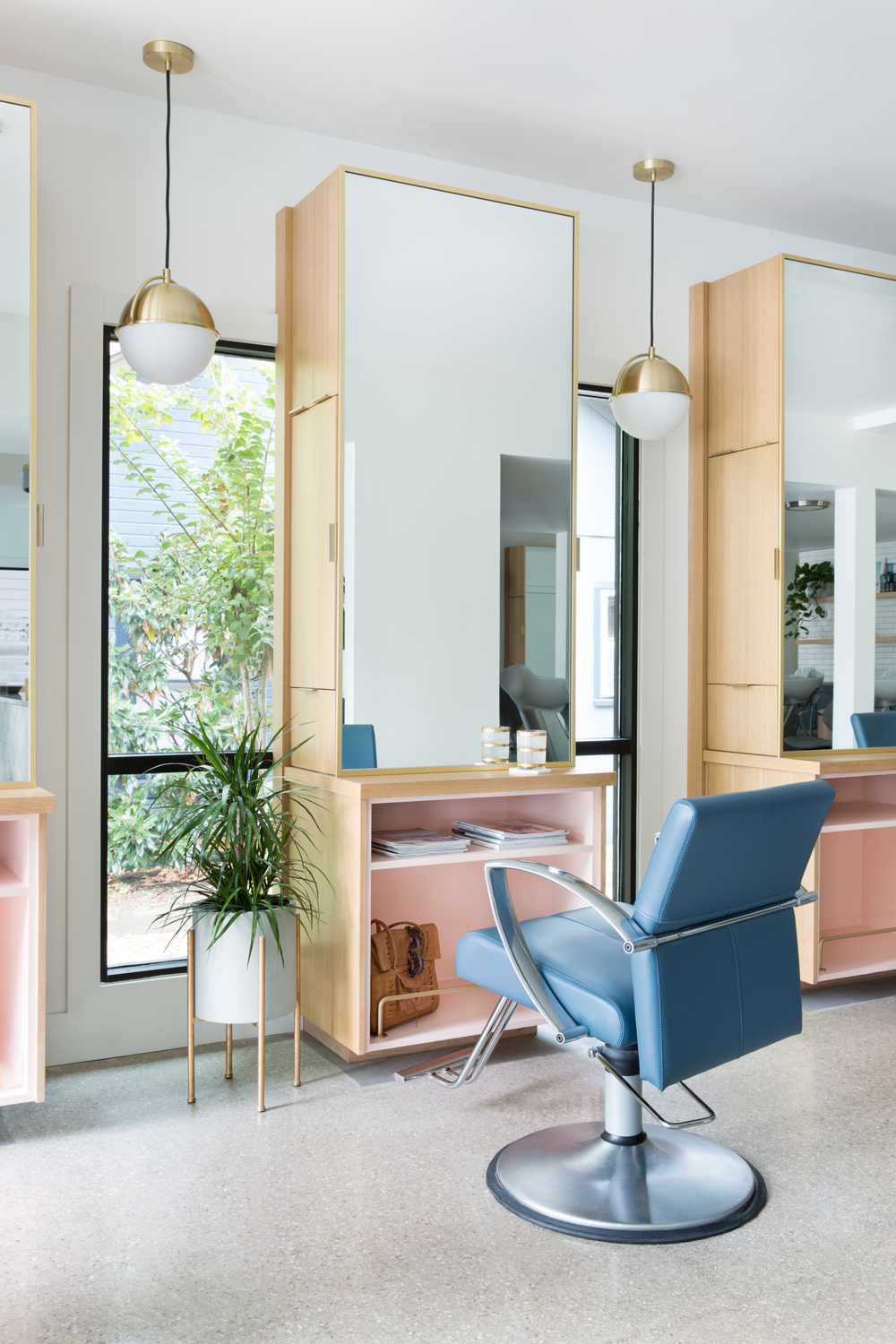 The blue chairs and the pink shelves at the stations in Mirror Mirror Salon in Austin, Texas, reflect the furniture color in the reception space.