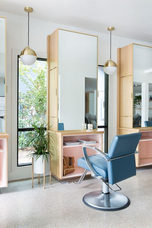 <p>The blue chairs and the pink shelves at the stations in Mirror Mirror Salon in Austin, Texas, reflect the furniture color in the reception space.</p>