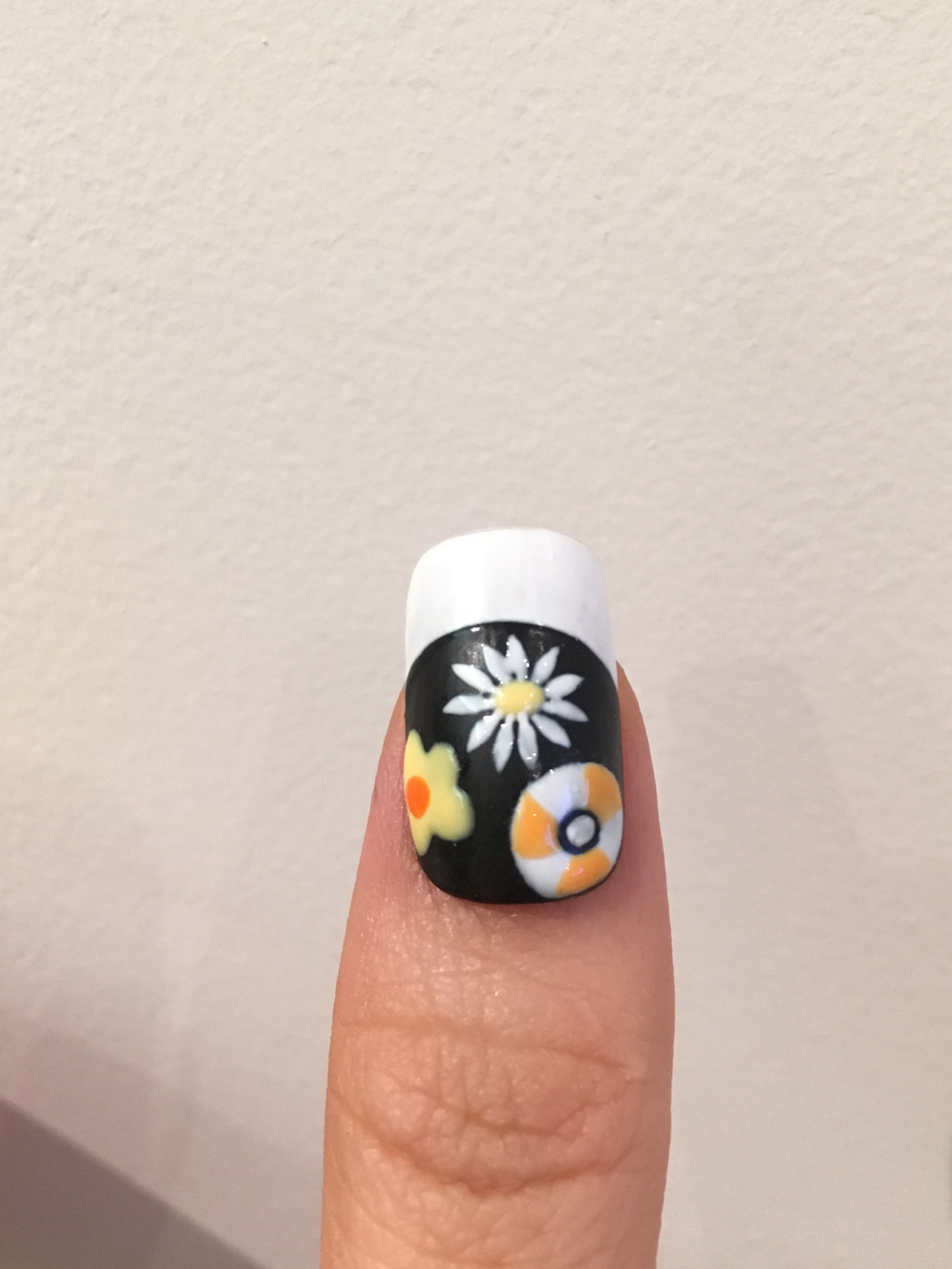 Draw petals of a daisy with white polish around the yellow dot, draw an orange dot on the yellow flower, and draw and orange pattern on the white circle.