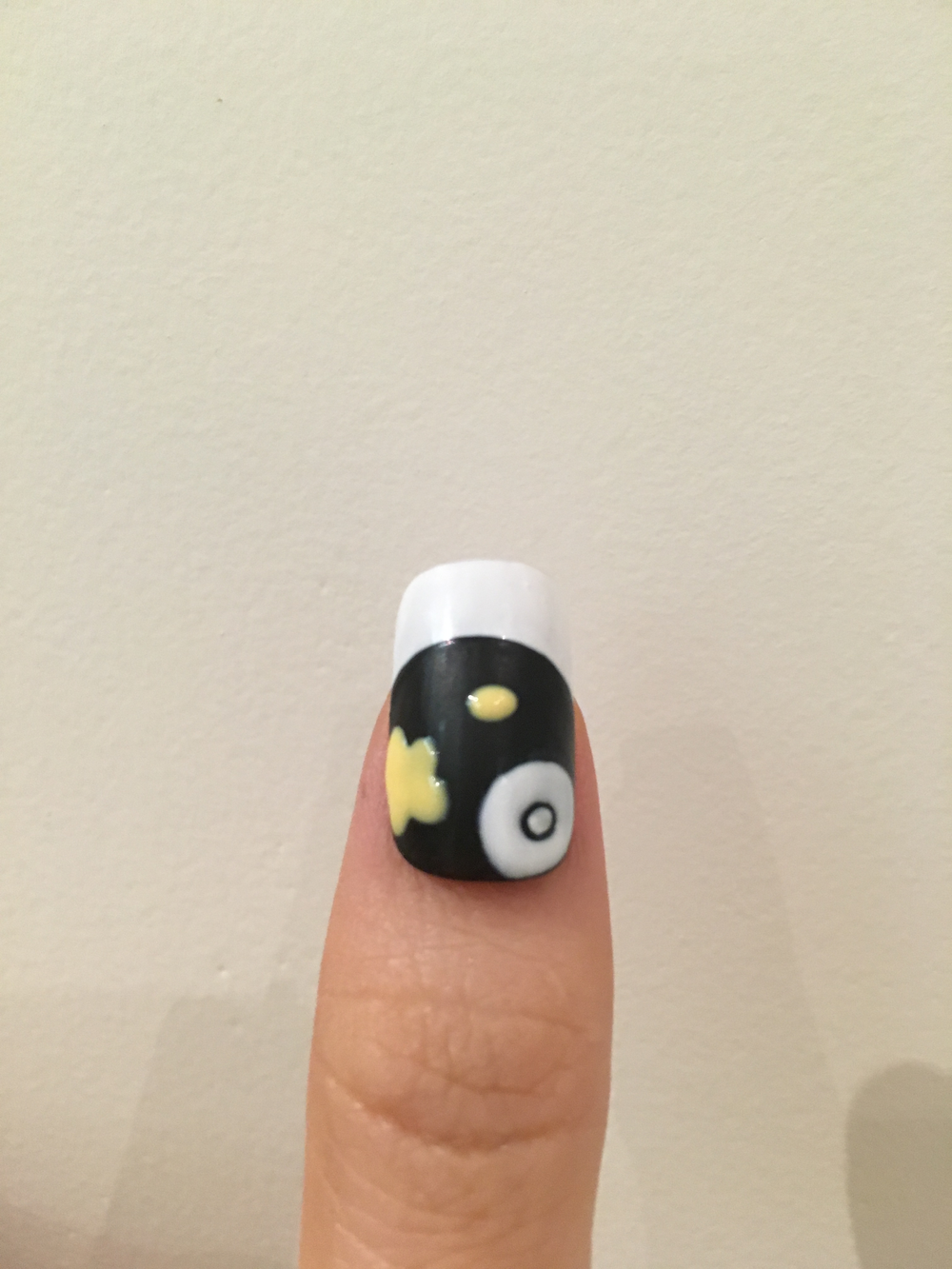 Draw a white dot on the bottom corner of the thumb, and draw a round circle around it. Draw a yellow dot and yellow petal on the same nail.