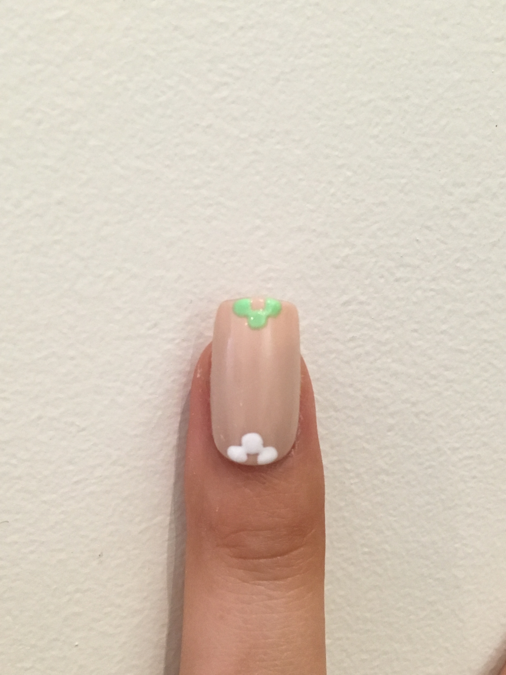 Draw three dots on the bottom and tip of the index, middle and pinky with white and light green polish.