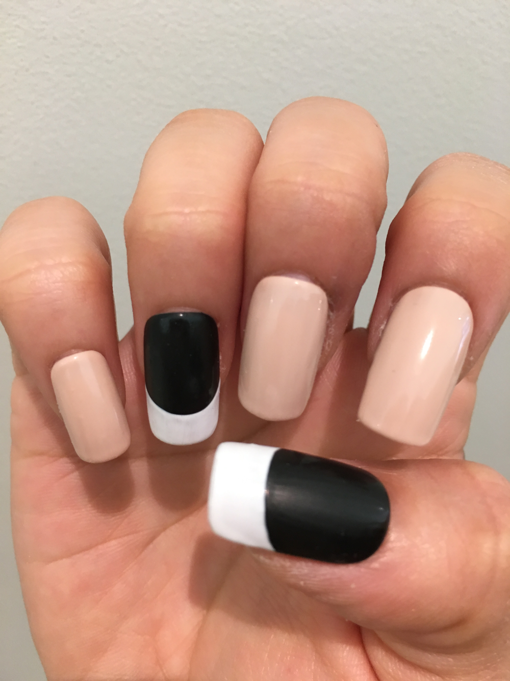 First apply base coat. Then, apply light beige polish on index, middle and pinky, and apply black polish on thumb and ring finger. Draw French line with white on thumb and ring finger.