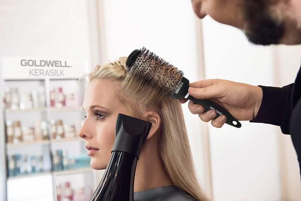 Power dry the hair up to 80% dry in the direction of the cuticle to elevate the root creating the required root direction. Cross section the hair. Using the round brush elevate the root and smooth through to the ends.