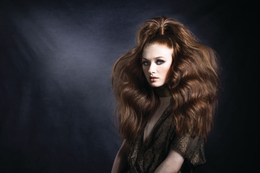 "<p>""Here the teasing is the star,"" Elias says. ""You don't get a 'gasp' reaction if it's just curled with an iron. Using a teasing comb and the Fingerbrush takes this look to the next level.""</p> <p>Gently brush and detangle hair with the Olivia Garden Fingerbrush. Create a v-shaped section on the crown. Brush into a slick top knot with an Olivia Garden Healthy Hair Ionic Combo brush. Secure. Take a 1/4"" section, smooth with the Olivia Garden Ceramic+ion Supreme Combo brush. Wrap hair around elastic and secure. Use the Olivia Garden CarboSilk technical comb to tease small sections of hair from the ends toward the scalp to form a cushion for added volume. Smooth the perimeter with the Supreme Combo brush and set with a workable spray. </p>"