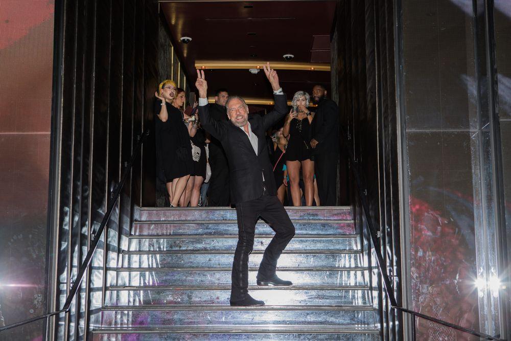 "<p><em>John Paul DeJoria flashes his signature peace sign walking into the evening party. </em></p> <p><em>""Whenever you do something for someone else your space in the universal will expand.""</em></p> <p><em>-John Paul DeJoria</em></p>"