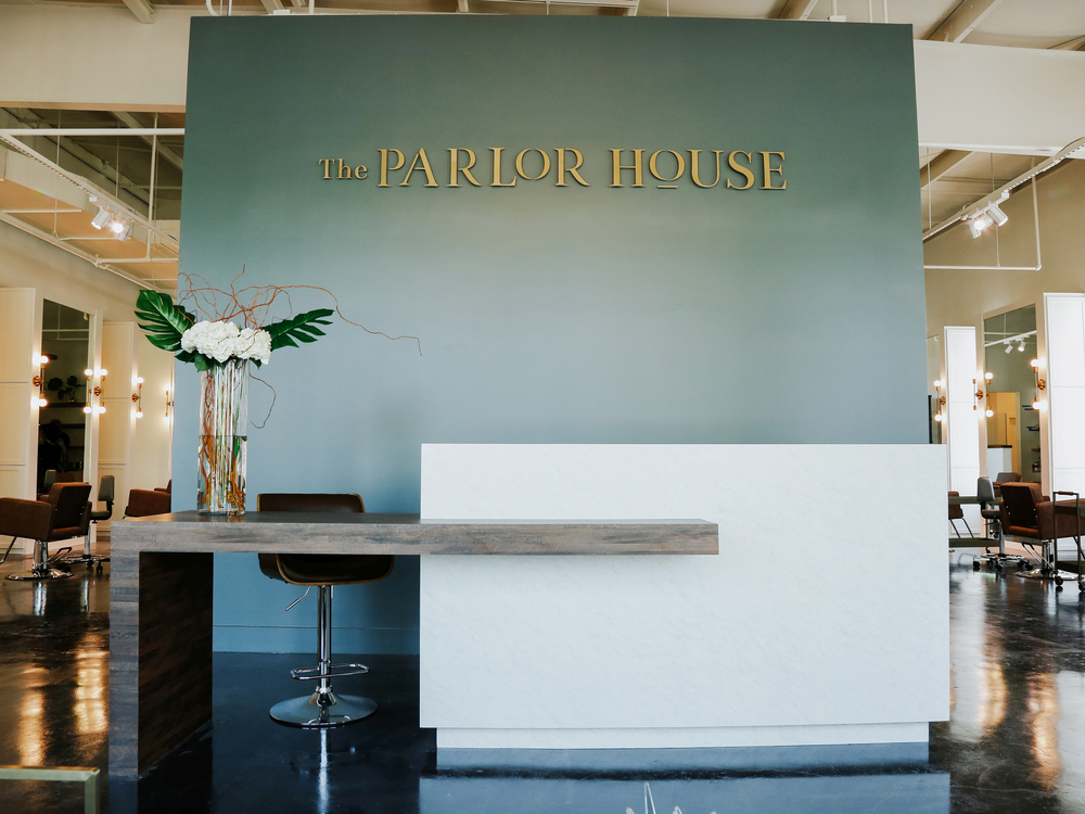 A soft sage green/gray wall provides the perfect contrast for the white reception desk at The Parlor Salon in Lake Charles, Louisiana.