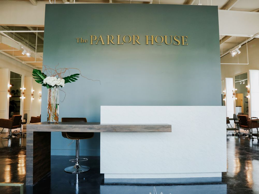 <p>A soft sage green/gray wall provides the perfect contrast for the white reception desk at The Parlor Salon in Lake Charles, Louisiana.</p>
