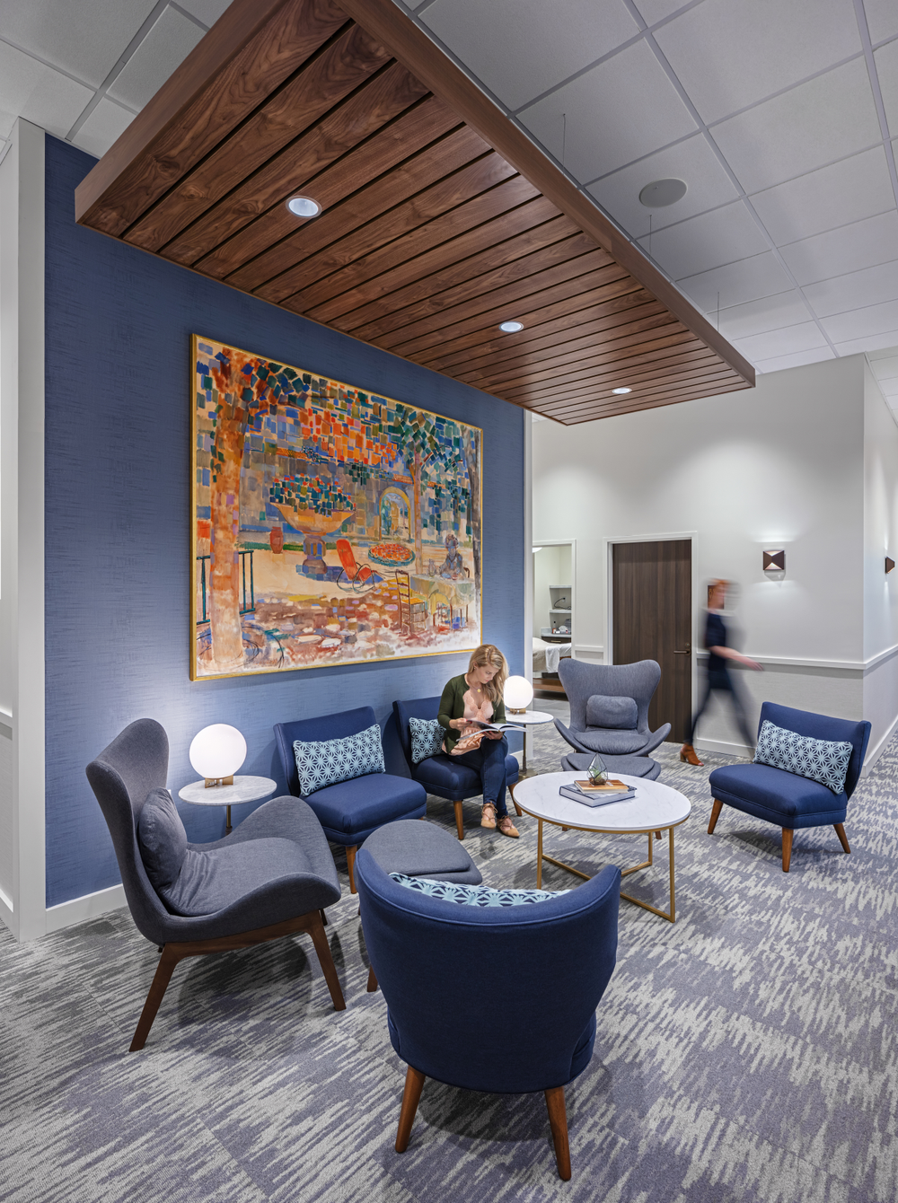 A bold blue wall, drop-planked ceiling and lavish artwork create a soothing place for clients to wait for a service.