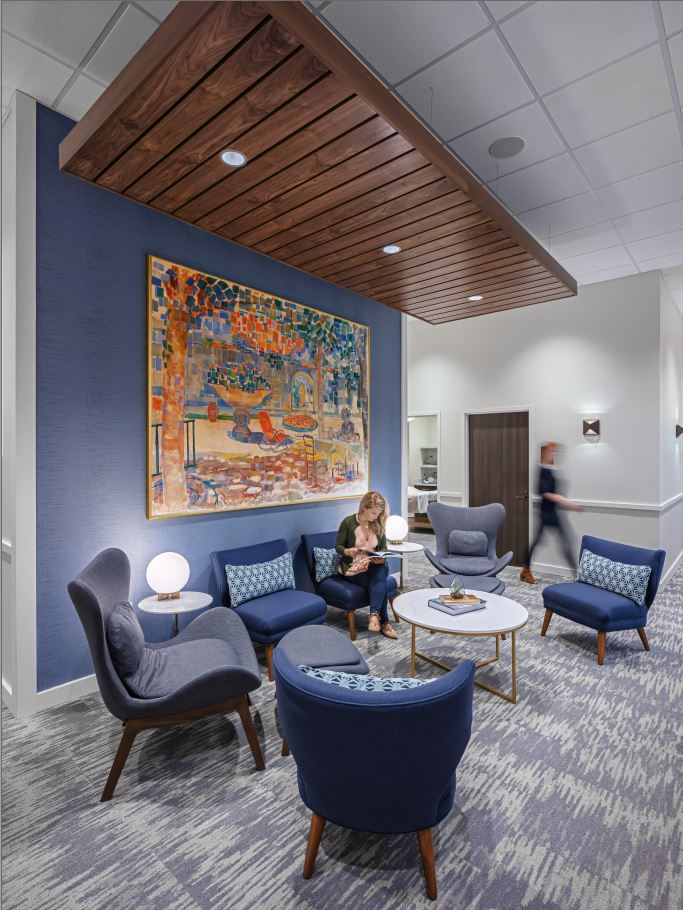 Lavish art, a wall of blue and matching furniture create a welcoming reception area for clients at Penzone Salon + Spa in Dublin, Ohio.
