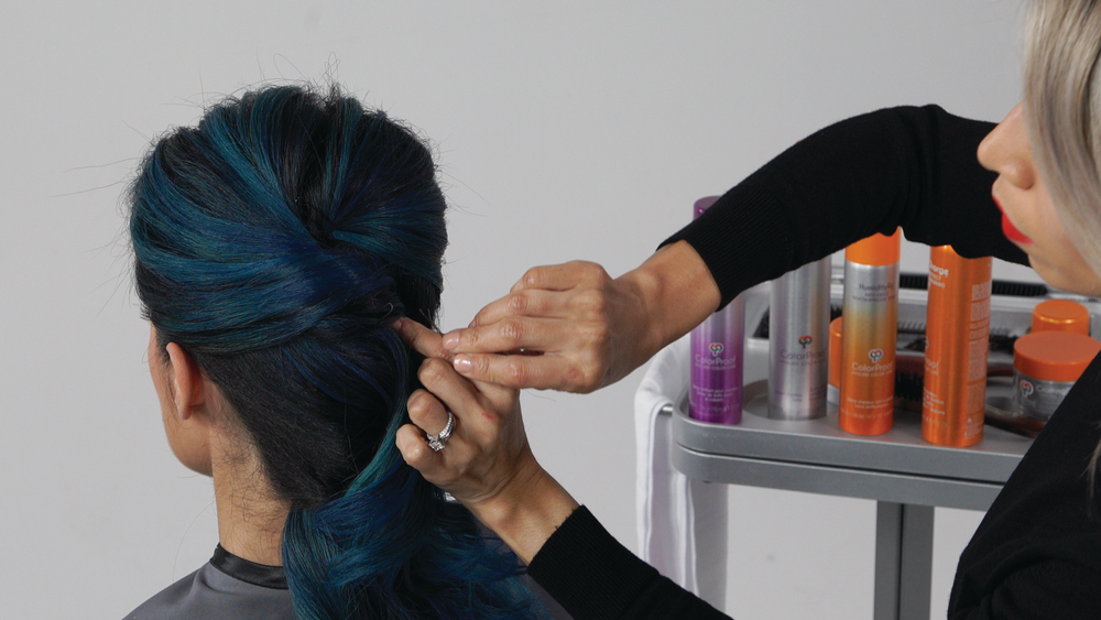 <p><strong>STEP 4 : </strong>Direct all hair in the back into a low, loose ponytail. Holding the elastic, twist and secure onto the back of the head in a French twist shape. </p>