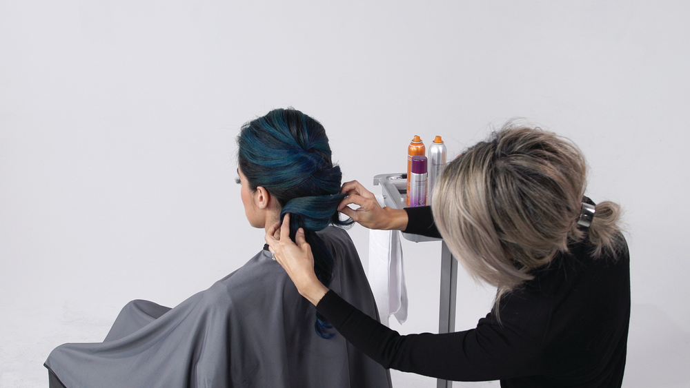 <p><strong>STEP 3 : </strong>Take a 2-3 inch triangular section at the nape and backcomb firmly to create a base using <strong>TextureCharge </strong>Color Protect Texture + Finishing Spray for support.</p>