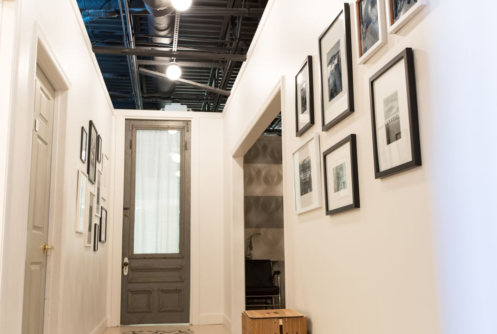 The gallery wall in the hallway leading to the washroom showcases images of Ryan's family and childhood in New Jersey. She plans to add family photos from the salon staff, as well.
